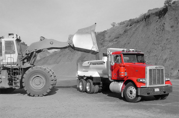 a construction site tractor loading a dump truck with dirt
